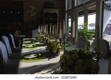 Shadows of candleholders lie on the white tablecloth between green plates