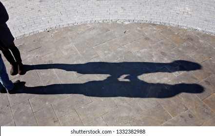 Shadows of couple in love on a walk in the city on sunny day. Man and women holding hands and looking on each other, city outdoor