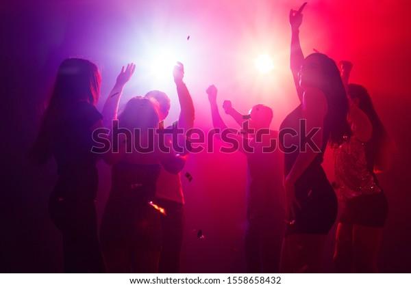 Sombras. Una multitud en silueta levanta las manos sobre la pista de baile sobre fondo de neón. Vida nocturna, club, música, baile, movimiento, juventud. Colores púrpura y rosa y niñas y niños en movimiento.