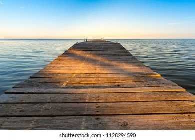Shadows cut across wooden jetty at sunset