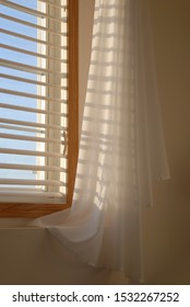 Shadows of the evening sun coming through window blinds leaves a soft shadow on draped sheer linen curtains