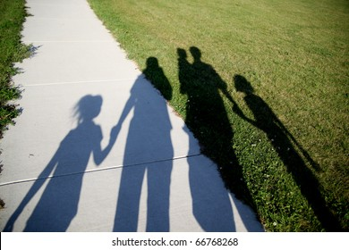Shadows of a family of five walking in the park holding hands