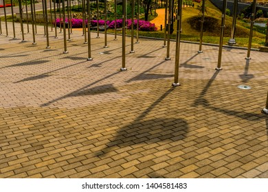 Shadows of flags on brick walkway between rows of chrome flagpoles in public park.