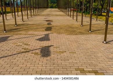 Shadows of flags on brick walkway between rows of chrome flagpoles.