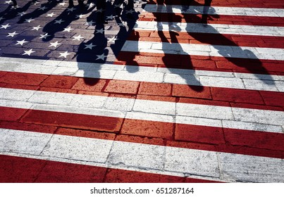 Shadows of group of people walking through the sunny streets with painted United States of America flag on the floor.