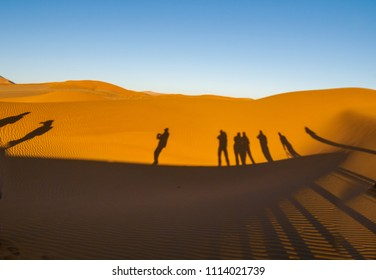 Shadows of group tourists in curve of dune at Hidden Vlei, Sossusvlei, Namibia.