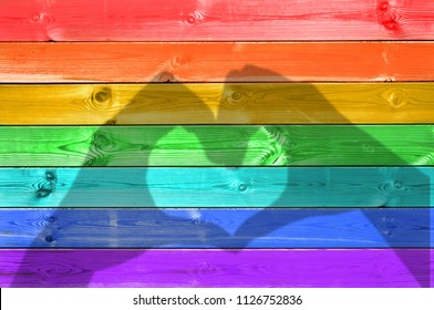 Shadows of hands forming a heart on colorful rainbow painted wood planks background, gay flag and love concept