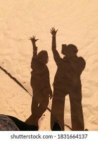 Shadows of happy humans on yellow sand floor