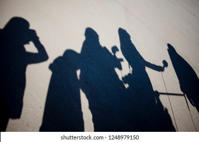 Shadows of journalists and photographers who interview