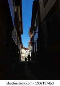 Shadows, light and silhouettes in Guimarães narrow street.