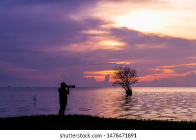 The shadows of men are holding a telephoto camera to take pictures of landscape landscapes. At Songkhla Lake, Pak Pra, Thale Noi Waterfowl ReservePhatthalung Canal