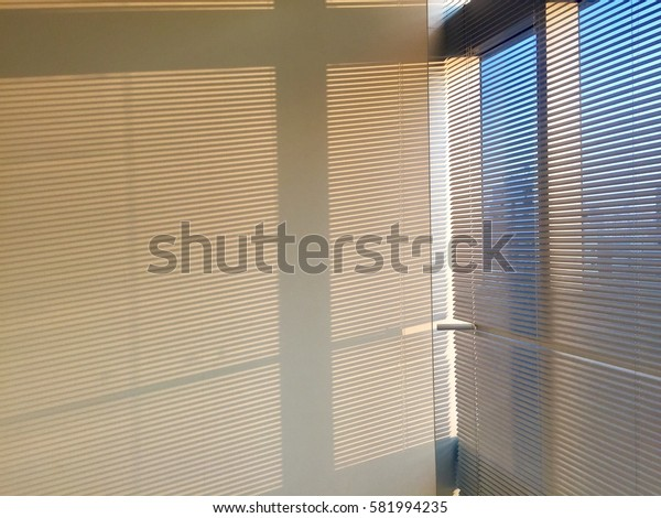 Shadows on the wall from curtain in the office.