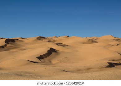 Shadows over sandy dunes back to back  in the Sahara desert in Tunisia