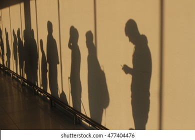 Shadows of people waiting in line talking and checking smartphones.