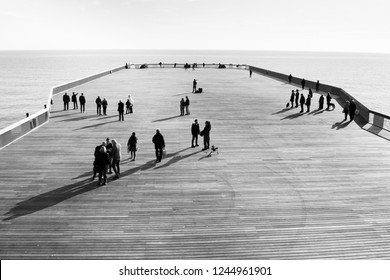 Shadows of people walking on Hastings Pier