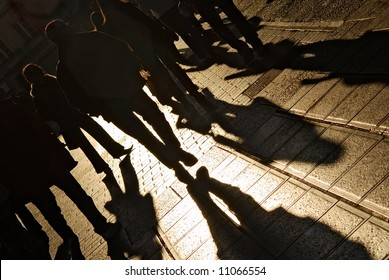 Shadows of people walking in a street of the city. The afternoon sun gives a warm and dramatic light.