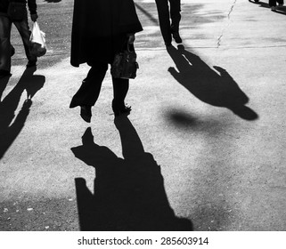 Shadows of people walking in a street in morning light