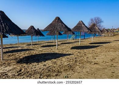 Shadows of reed umbrellas on an empty beach