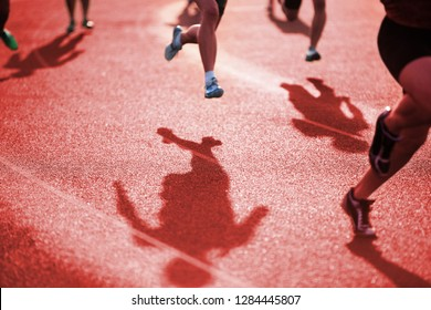 Shadows of runners racing around the curve in a track and field race, shallow focus in center of image