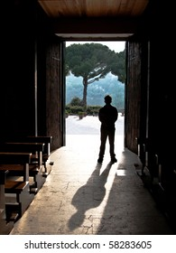 shadows of a silhouetted man in a church doorway