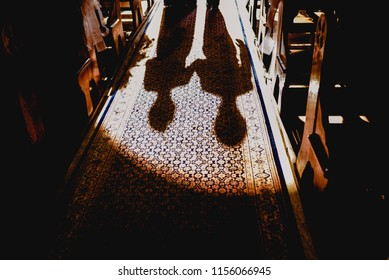 Shadows and silhouettes of bride and groom entering the church.