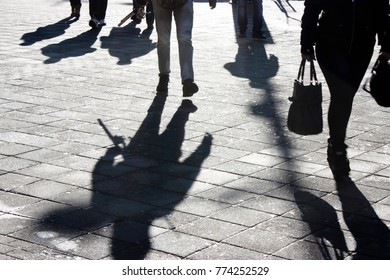 Shadows and silhouettes of people walking the city street in winter in black and white