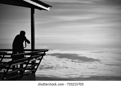 The shadows of tourists are taking pictures on the porch of the morning house with mist and sky as the background. Phetchabun Attractions in Thailand. Black and white. Copy space.