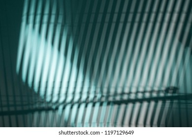 THE SHADOWS FROM THE WOODEN BLINDS ON A WALL