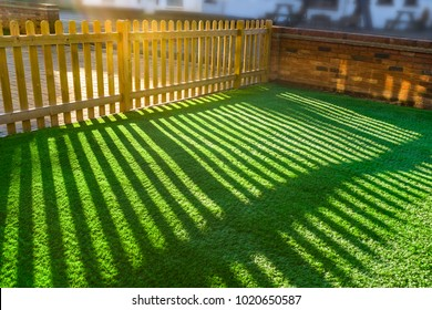 shadows of  a wooden picket fence in a front yard, front garden with artifical grass as a lawn and a red brick perimiter wall.
