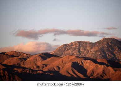 Shadowy desert sunrise with hint of dark clouds over orange-colored terrain.