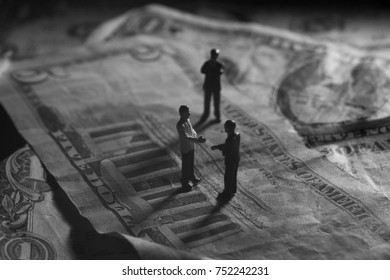 A shady business deal depicted in miniature. Corrupt politicians or business people make a deal in the shadows. Concept of bribery, corruption, law, and money. White collar crime on Wall Street.