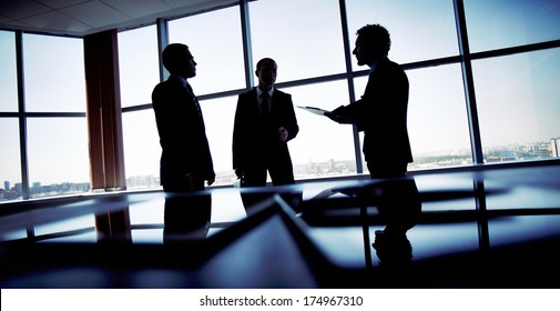 Shady image of a manager discussing business matters with his subordinates