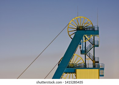 Shaft tower with wheels and ropes at dusk.
