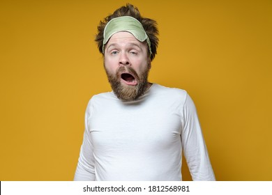 Shaggy, bearded man with a sleeping mask on his head yawns amusingly. Yellow background.