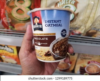 Shah Alam, Malaysia - 24 January 2019 : Hand hold a cup of QUAKER Instant Oatmeal flavour chocolate for sell in the supermarket.