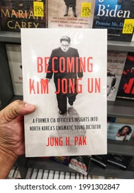 Shah Alam, Malaysia - 29 May 2021 : Hand hold a book title BECOMING KIM JONG UN by Jung H Pak for sell in the book stores with selective focus.