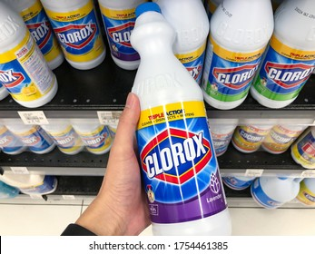 SHAH ALAM, MALAYSIA - JUNE 4, 2020: Close up of hand holding a bottles of Clorox Bleach in grocery store. Clorox is an American Company founded in 1913.