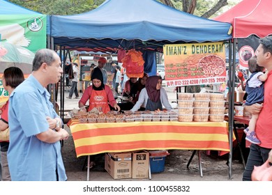SHAH ALAM, MALAYSIA - MAY 27, 2018: Vendors at their mini donut stall in a Ramadan food bazaar in Shah Alam. The food bazaar is established for Muslim to break fast during the holy month of Ramadan.