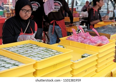 SHAH ALAM, MALAYSIA - MAY 27, 2018: A vendor packs traditional glutinous cakes at her stall in a Ramadan food bazaar in Shah Alam. The bazaar is established for Muslim to break fast during Ramadan.