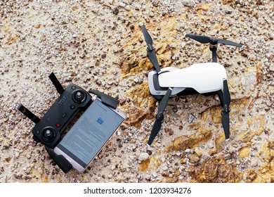 Shah Alam, Malaysia - October 14, 2018: Drone white color with controller on the ground. Updating latest firmware before flight