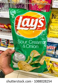 Shah Alam, Selangor, Malaysia- May 09, 2018; Hand hold potato chips packet LAY'S SOUR CREAM and ONION at supermarket.