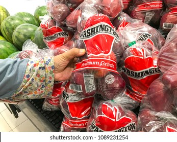 Shah Alam, Selangor, Malaysia- May 09, 2018; Hand pick up packet red apple in the supermarket.