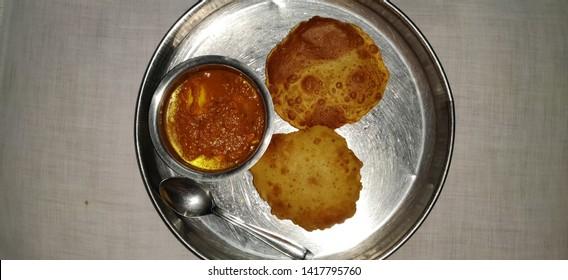 Shahi paneer with Puri or poori. Indian gujarati food puri or poori. Homemade Indian Potato Poori or Puri served with Shahi paneer.