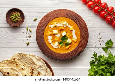Shahi paneer traditional Indian vegetarian masala gravy meal vegetables, white sauce and butter paneer in clay bowl