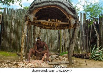 Shakaland Zulu Cultural Village, KwaZulu-Natal, South Africa - December 2016: man in traditional clothes wood crafting