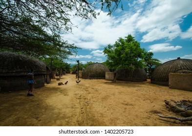 Shakaland Zulu Cultural Village, KwaZulu-Natal, South Africa - December 2016: Zulu woman in village courtyard, chickens graze