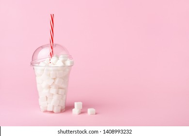 Shake glass with straw full of sugar cubes on pastel pink background. Unhealthy diet concept. Minimal, copy space, side view.
