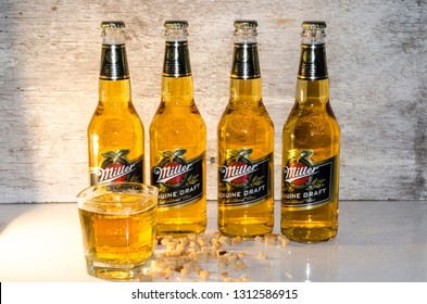 SHAKHTERSK, RUSSIA - FEBRUARY 13, 2019: Miller genuine draft beer on a wooden background with a glass of fresh beer and crackers. A product of the Miller Brewing Company owned by SABMiller.
