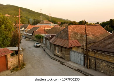 Shaki, Azerbaijan - August 13, 2018. Street view in Shaki, Azerbaijan, with historic brick buildings with tiled roofs and cars, at dusk.