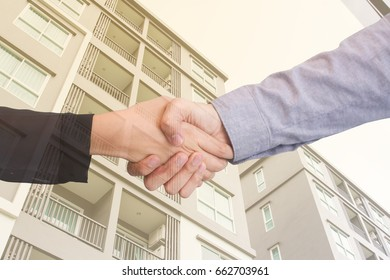 Shaking hand concept business cooperate with modern building background.